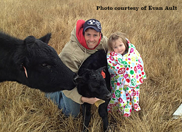 photo of Evan Ault and daughter with a calf.